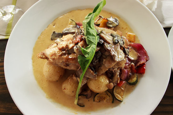Chicken Supreme on a bed of sauteed new potatoes served with roast vegetables and brandy & mushroom jus