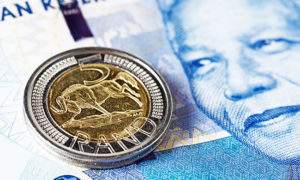 Five Rand coin rests on new Mandela South African banknote